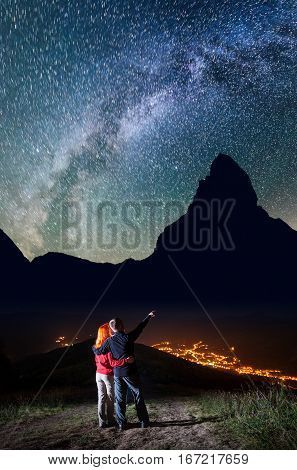 Romantic Male Tourist Embracing Red-haired Girl And Shows On Stars And Milky Way In Beautiful Starry