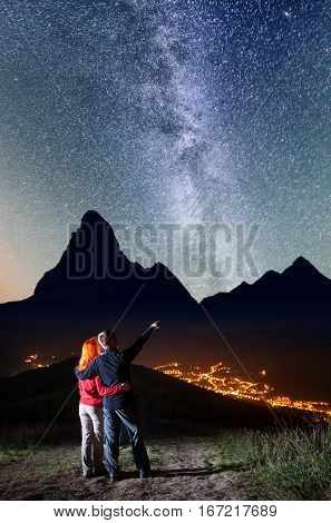 Romantic Guy Embracing Red-haired Girl And Shows On Stars And Milky Way In Beautiful Starry Sky At N