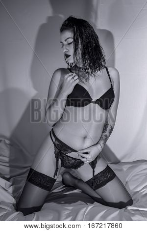 Young woman posing in black lingerie on bed, B&W