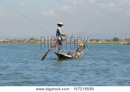 INLE LAKE, MYANMAR - DECEMBER 20, 2016: A fisherman in a boat unravels the fishing network