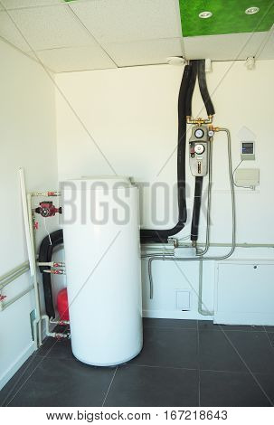 Boiler & Heating System Controls. Household boiler room with a new modern gas boiler heating electric warm water system and pipes. Boiler Controls and Thermostats.