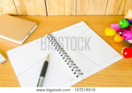 Smart phone, alarm clock,and notebook on wooden background