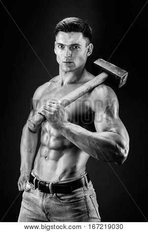 Muscular man with naked torso holding big hammer. Isolated on dark grey background