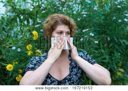 Woman with allergic rhinitis by a pollen