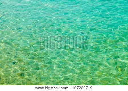 Photo of clear turquoise seawater surface texture