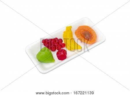 Several jelly candies gelatin based in the shape of different fruits in a small plastic tray on a light background