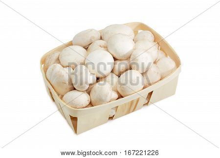 Fresh cultivated common button mushrooms in the wooden basket on a light background