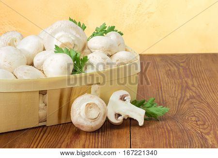 Fragment of wooden basket with fresh cultivated button mushrooms and twigs of parsley one whole mushroom and one half of mushroom separately beside on an old wooden surface