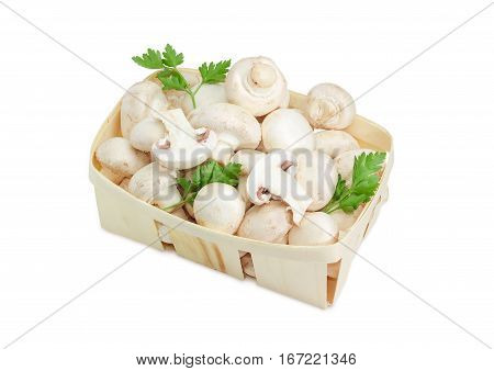 Fresh cultivated common button mushrooms and twigs of parsley in the wooden basket on a light background