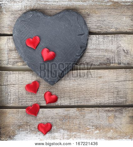 Stone heart symbol on old wooden background