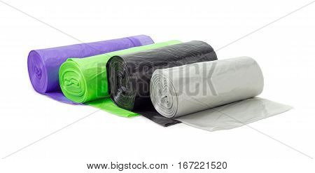 Several rolls of plastic disposable garbage bags of different sizes and colors including biodegradable on a light background