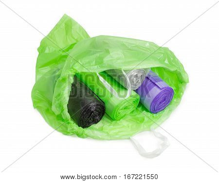 Several rolls of plastic disposable garbage bags of different sizes and colors in an open green garbage bag with handles made from ribbons on a light background