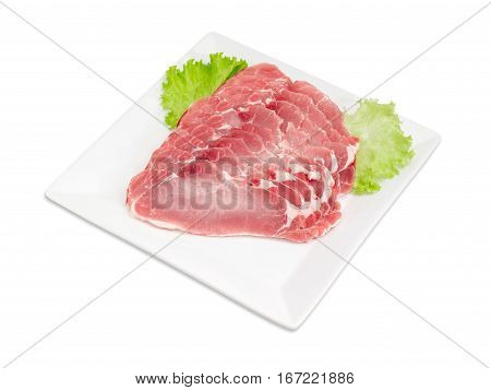 Sliced fresh chilled pork loin with lettuce leaves on a square white dish on a light background