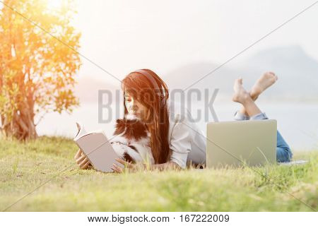 woman relaxing with puppy dog at public park