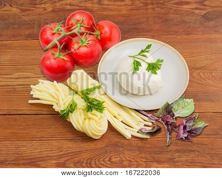 Piece of the fresh mozzarella cheese on the saucer two portion of the mozzarella cheese twisted to form a plait cluster of tomatoes and twigs of parsley and purple basil on an old wooden surface
