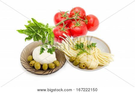 Ball of the fresh mozzarella cheese on the glass saucer mozzarella cheese twisted to form a plait on the other saucer green olives tomatoes basil and twigs of parsley on a light background