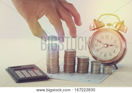 hand holding money on pile of coins and alarm clock concept in save grow and success in business by taking and spending time