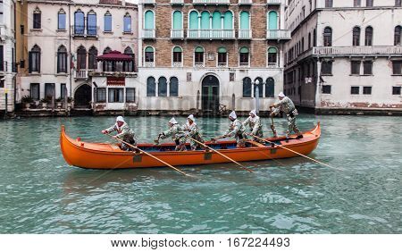 VeniceItaly- February 19 2012: A red boat with a group of funny disguised people sailing on the Grand Canal in a boats parade during the Carnival days.