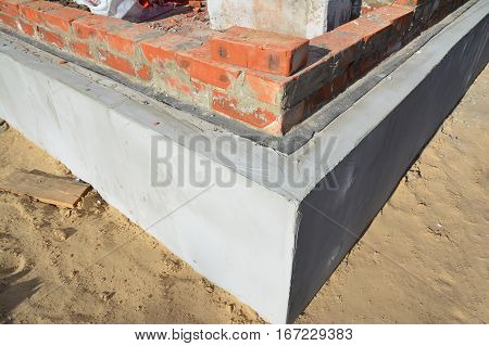 Foundation Insulation with bitumen waterproofing membrane brick wall to avoid dampness. Bricklaying Brickwork Building Brick House Wall.