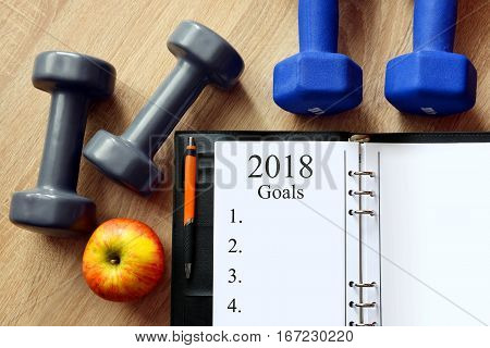 Dumbbells with apple and open notebook on wooen desk. Healthy resolutions for the New Year 2018.