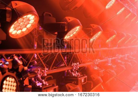 Stage lighting equipment. Red concert spotlight. The direct rays of light in the haze.