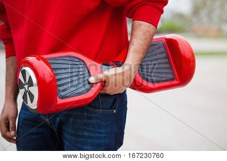 Boy holding modern red electric mini segway or hover board scooter in hands. Trending new transportation technology that produces no air pollution to the atmosphere. African male model close up on device