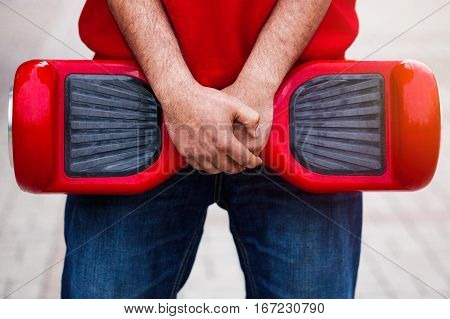 Man holding modern red electric mini segway or hover board scooter in hands. Trending new transportation technology that produces no air pollution to the atmosphere. African male model close up on device