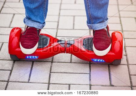 Feet of a woman riding on modern red electric mini segway or hover board scooter. Trending new transportation technology that is so much fun and easy to ride and produces no air pollution to the atmosphere. Close up on model legs and gadget.
