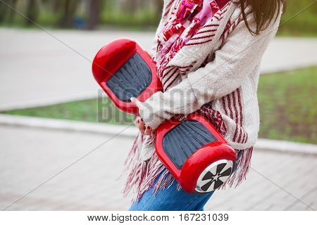 Woman holding modern red electric mini segway or hover board scooter in hands while walking in the park. Popular new transportation technology that produces no air pollution to the atmosphere. Girl is wearing trending boho style clothes.
