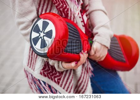 Womanl holding modern red electric mini segway or hover board scooter in hands while walking in the park. Popular new transportation technology that produces no air pollution to the atmosphere. Girl is wearing trending boho style clothes.