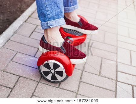Close up on feet of a gir in marsala shoes riding on a modern red electric mini segway or hover board scooter. Trending new transportation technology that is so much fun and easy to ride and produces no air pollution to the atmosphere.
