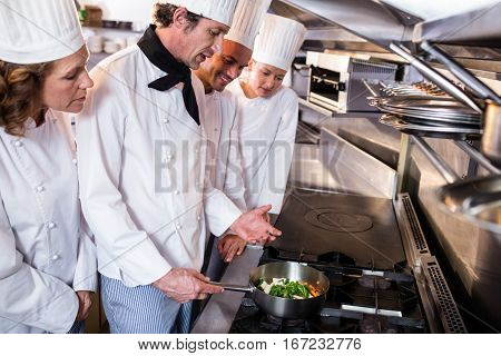 Experienced head chef explaining to his colleagues in the kitchen