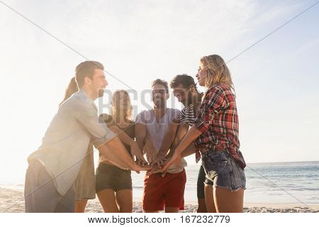 Happy friends gathering hands on the beach