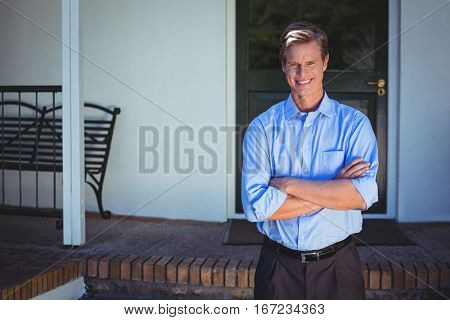 Handsome businessman standing with arms crossed in front of a house