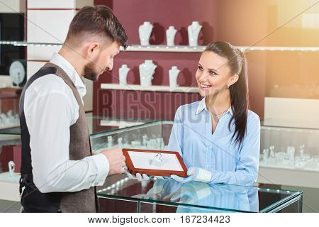 Young jeweler brunette girl holding in hands and showing for handsome man engagement ring with blue stone. Looking each other, talking and smiling. Male thinking and choosing jewelry in luxury store.