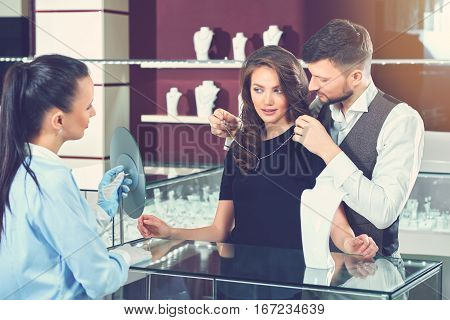 Handsome young man trying necklace for his gorgeous wife at jewelry store. Jeweler in gloves holding mirror for buyer. Brunette woman with wavy hair, wearing black dress estimating looking at mirror.