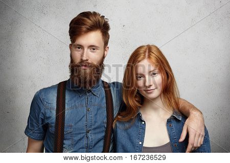 Beautiful Young Caucasian Couple Posing Indoors. Handsome Stylish Man With Fuzzy Beard Hugging His A