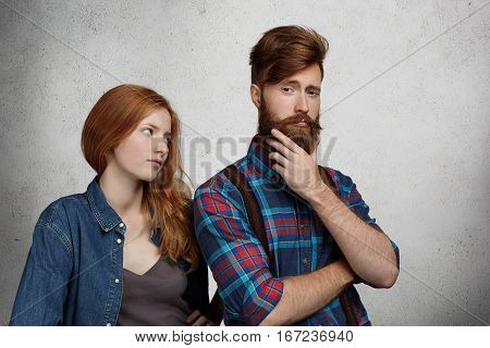 Young Redhead Female In Denim Jacket Staring Angrily At His Narcissistic Boyfriend Who Is Having Sel