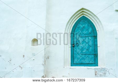 Architecture background - old metal door on the white stone wall. Architecture background with architecture building details