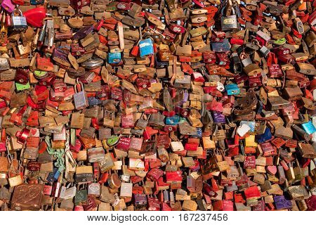 Cologne, Germany - January 19, 2017: A cluster of love locks on Hohenzollern Bridge. As proof of their love couples fix padlocks to the bridge railings and throw the key into the river below.