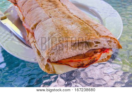 big sandwich made with spanish bread loin of pork and cheese. In Spain sandwich is known as bocadillo or bocata