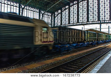 A goods train or freight train in motion on a train station. Motion blur