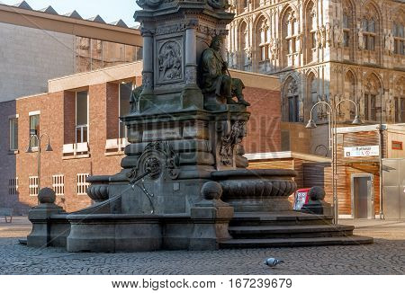 Cologne, Germany - January 19, 2017: Fragment of the fountain-monument of Jan von Werth. In the background the tower of City Hall and the entrance to the metro station.