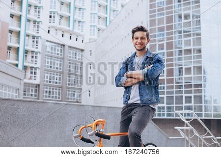 Man riding a bicycle outside. Smiling handsome young guy with beard in jacket looking at camera. He is standing on a bike with crossed hands. Urban background