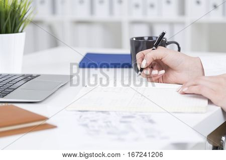 Close up of female hand writing in copybook placed on white desktop with coffee cup laptop and other items. Young accountant writing down data