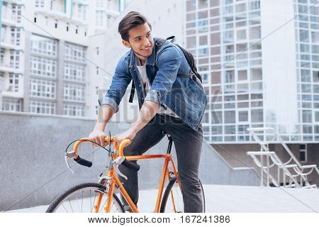 Man riding a bicycle outside. Happy cycling boy with his rucksack. He is having fun. Urban background