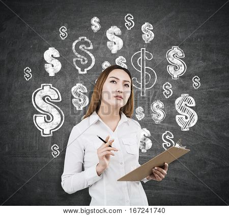 Attractive asian woman on chalkboard background with drawn dollar signs. She is thinking about financial growth