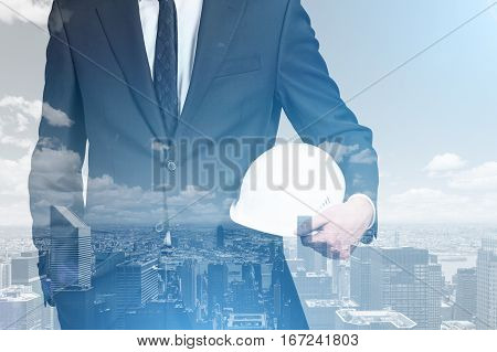 Abstract image of young businessman with helmet on abstract city background. Workers security concept. Double exposure