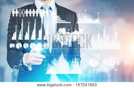Businessman pointing at hi-tech panel with business charts and diagrams. Modernisation concept