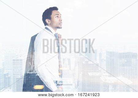 Side view of thoughtful african american busiessman on city background. He is thinking about employment. Double exposure